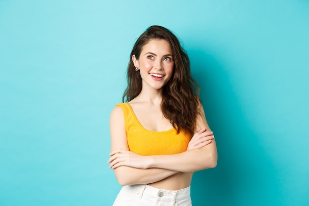 Conceito de verão e estilo de vida, jovem mulher pensativa cruza os braços no peito e olhando para o lado superior esquerdo.