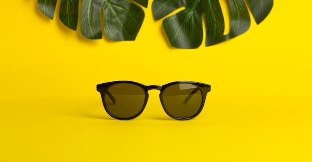 Conceito de verão e férias. óculos de sol e folhas tropicais em um fundo colorido amarelo