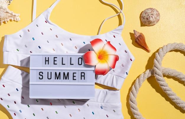 Conceito de verão e férias. palavras olá verão na mesa de luz com maiô, folhas tropicais e conchas planas sobre fundo laranja