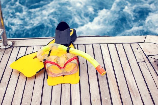 Conceito de verão e férias. vista do mar. máscara de mergulho e nadadeiras lelft no barco.