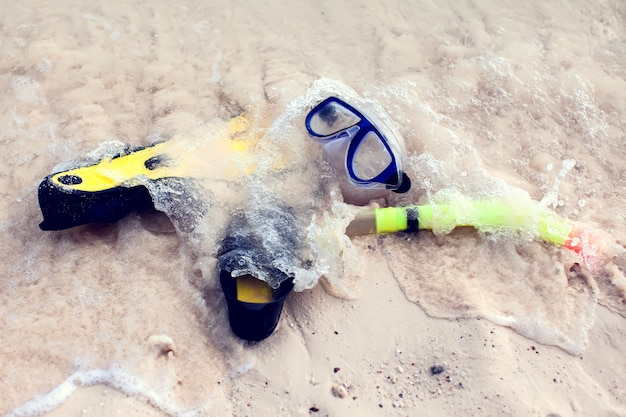 Conceito de verão e férias. vista para a praia. máscara de mergulho e nadadeiras lelft na areia