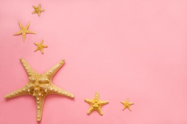 Conceito de verão flat lay. estrelas do mar sobre o fundo rosa. conceito de vistas superiores de verão com espaço de cópia.