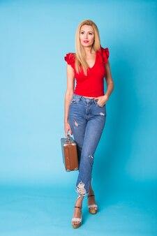 Conceito de verão, moda e férias - linda mulher loira com mala retrô na parede azul.
