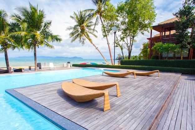 Conceito de verão, viagens, férias e férias - guarda-chuva e cadeira com piscina no resort do hotel