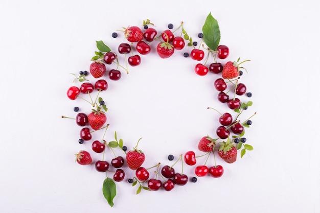 Conceito de verão. vista plana leiga, superior, cópia espaço. moldura feita de frutas frescas. morango, mirtilo e cereja doce