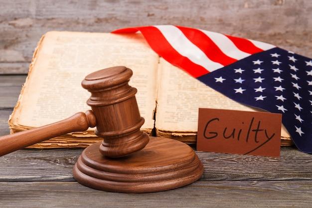 Conceito de veredicto de culpado no tribunal dos eua. martelo do juiz de madeira com o velho livro de leis e a bandeira americana.
