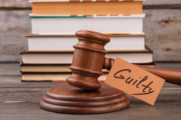 Conceito de veredicto de gulity. martelo de madeira e pilha de livros.