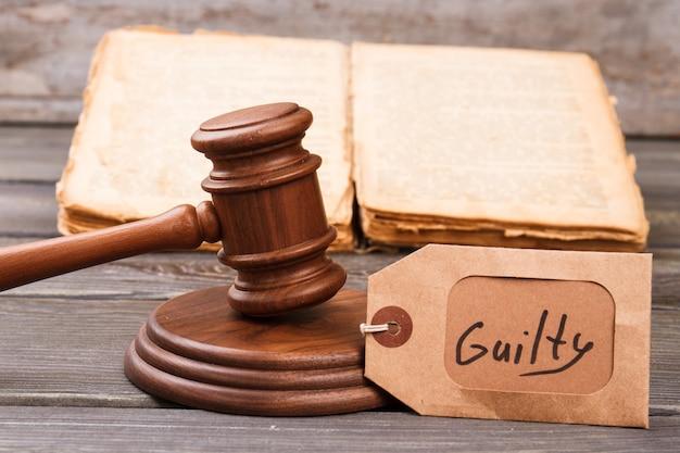 Conceito de vértice culpado no tribunal. martelo de madeira e um livro antigo.
