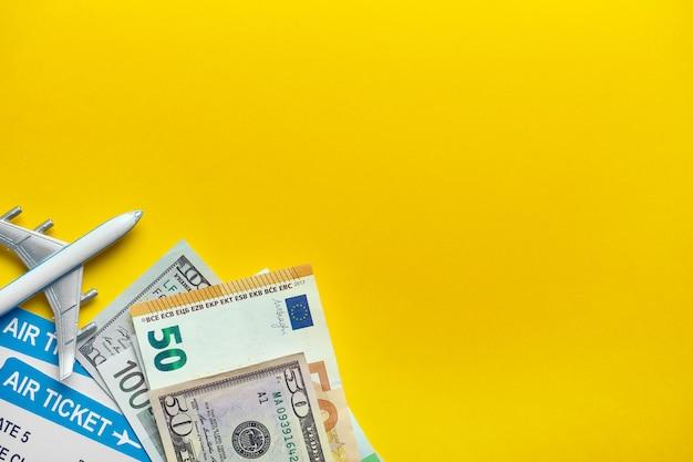 Conceito de viagem aérea com bilhetes e dinheiro em um fundo amarelo com espaço de cópia