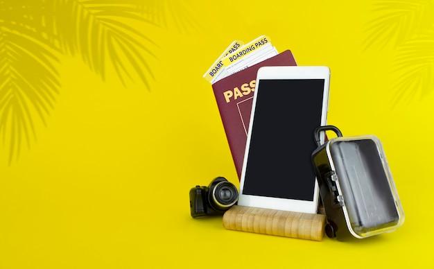 Conceito de viagem aérea, passaporte, cartão de embarque, malas e smartfone em fundo amarelo