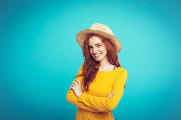 Conceito de viagem - close up retrato jovem e bonita menina redhair atraente com chapéu de moda e sorvete sorrindo. fundo pastel azul. copie o espaço.