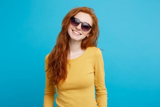 Conceito de viagem - close up retrato jovem e bonito atraente gengibre menina cabelo vermelho com sorvete na moda sorrindo. fundo pastel azul. copie o espaço.
