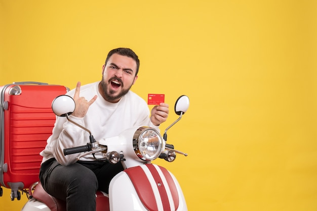 Conceito de viagem com jovem louco emocional engraçado viajando sentado na motocicleta com a mala segurando o cartão do banco em amarelo
