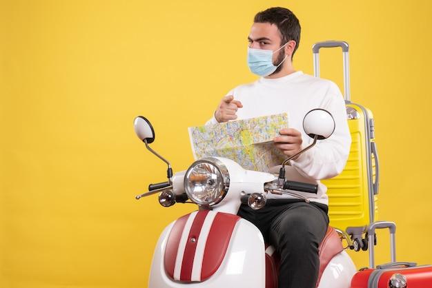 Conceito de viagem com um cara confiante em uma máscara médica sentado em uma motocicleta com uma mala amarela e segurando um mapa apontando para a frente em amarelo