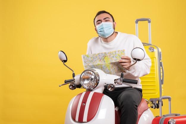 Conceito de viagem com um cara curioso com máscara médica sentado em uma motocicleta com uma mala amarela e segurando um mapa amarelo