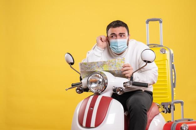 Conceito de viagem com um jovem curioso em máscara médica sentado em uma motocicleta com uma mala amarela e segurando o mapa