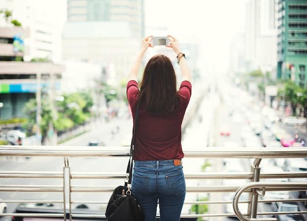 Conceito de viagem da vida urbana da fotografia da opinião traseira da mulher