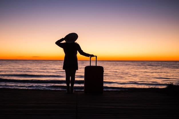 Conceito de viagem, férias e viagem de verão - silhueta de mulher jovem com vestido de verão e chapéu, olhando para o mar.