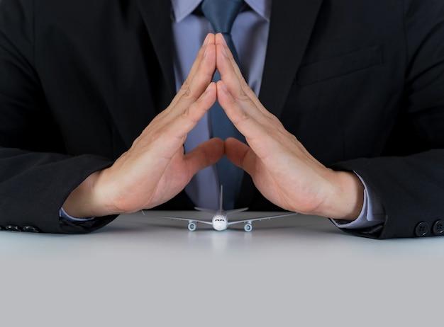 Conceito de viagem seguro, mãos apoiar modelo de avião em cima da mesa