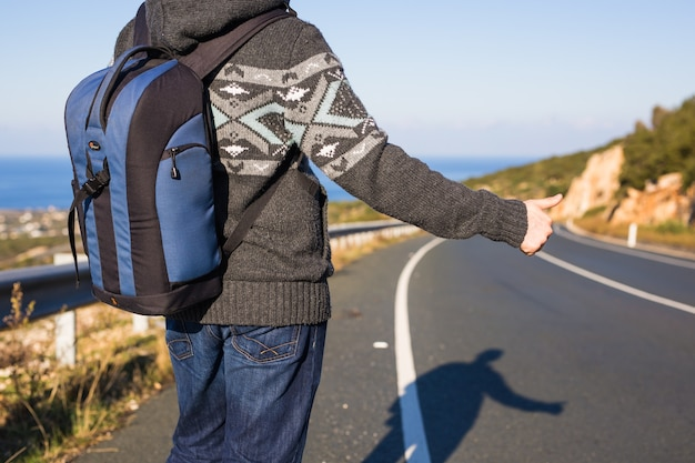 Conceito de viagem, viagem, gesto e pessoas - homem pedindo carona e parando o carro com os polegares para cima gesto na zona rural.