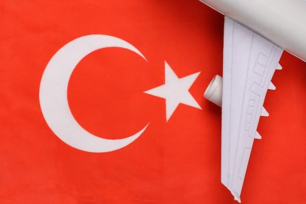Conceito de viagens. asa de avião de passageiros contra o fundo da bandeira turca