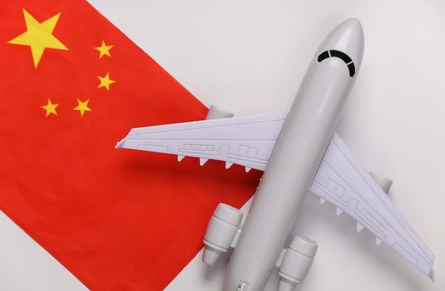 Conceito de viagens. avião de passageiros e bandeira da china em fundo branco