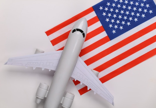 Conceito de viagens. avião de passageiros e bandeira dos eua em fundo branco