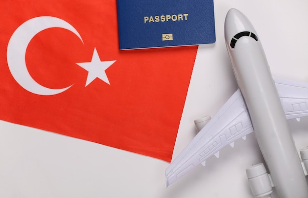 Conceito de viagens. avião de passageiros, passaporte e bandeira turca em fundo branco
