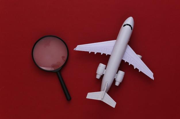 Conceito de viagens. avião e lupa em vermelho