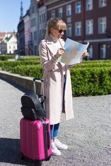 Conceito de viagens - bela jovem viajante com mala perdida na cidade