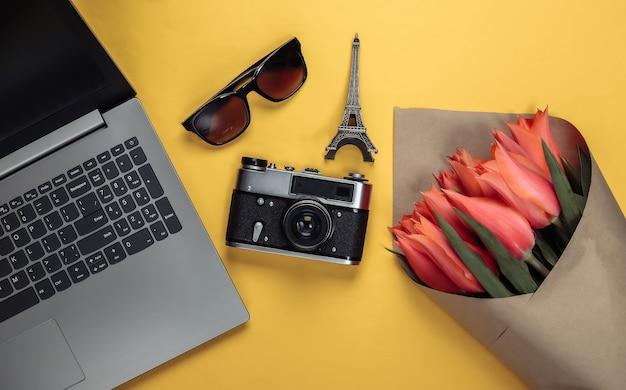 Conceito de viagens. buquê de tulipas, câmera, estatueta da torre eiffel, laptop e óculos escuros em amarelo