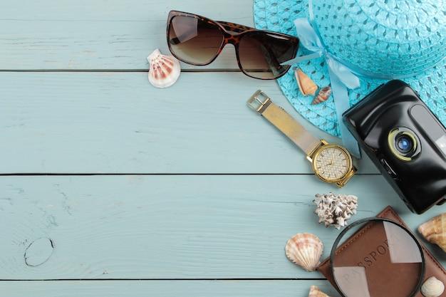 Conceito de viagens chapéu, câmera, passaporte e óculos de sol sobre uma mesa de madeira azul. vista do topo.