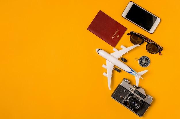 Conceito de viagens com avião de brinquedo, câmera vintage, passaporte em um fundo amarelo.