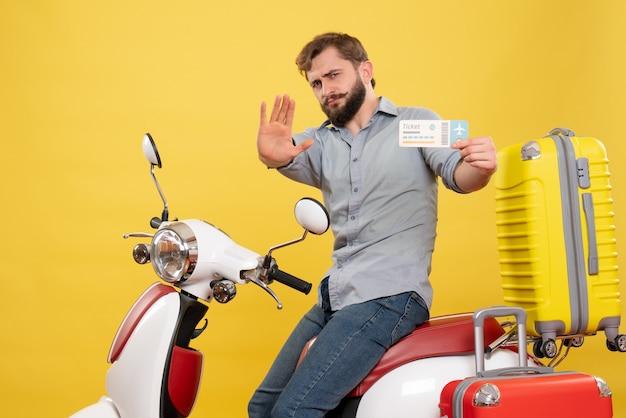 Conceito de viagens com jovem barbudo emocional sentado na moto e mostrando cinco segurando o bilhete amarelo