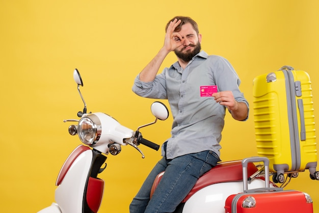 Conceito de viagens com jovem barbudo emocional sentado na moto e segurando o cartão do banco, fazendo gestos de óculos sobre ele em amarelo