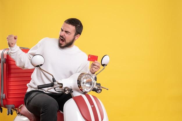 Conceito de viagens com jovem orgulhoso e ambicioso viajando sentado em uma motocicleta com uma mala segurando um cartão de banco em amarelo