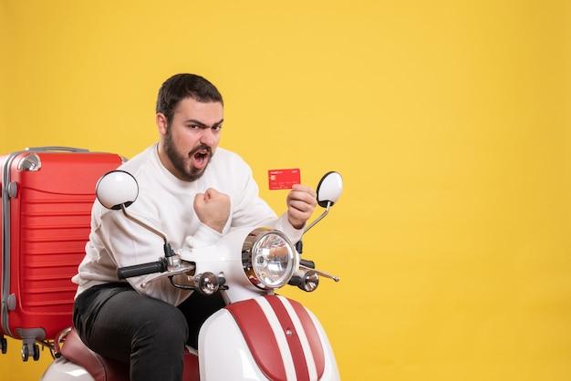 Conceito de viagens com jovem viajante emocional ambicioso sentado em uma motocicleta com uma mala segurando o cartão do banco em amarelo