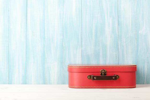 Conceito de viagens com mala de estilo retro em fundo azul de madeira.