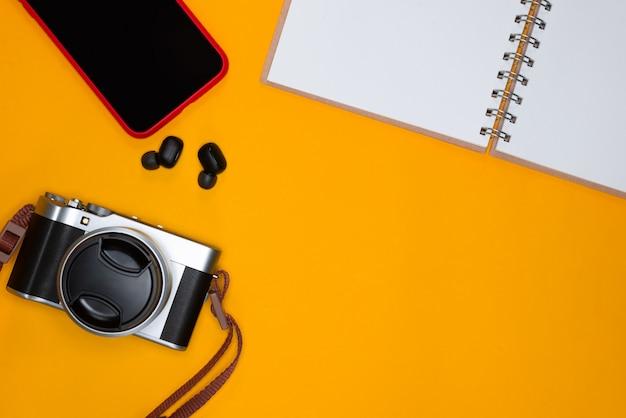 Conceito de viagens com nota de câmera e smartphone em fundo laranja