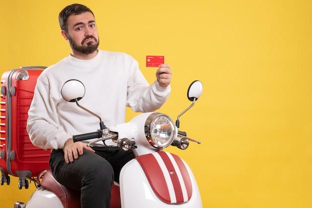 Conceito de viagens com o jovem confuso viajando sentado em uma motocicleta com uma mala segurando o cartão do banco em amarelo