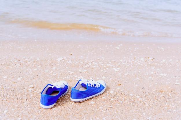 Conceito de viagens com tênis azul na praia