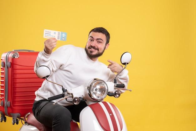 Conceito de viagens com um homem confiante sentado em uma motocicleta com uma mala mostrando o bilhete amarelo