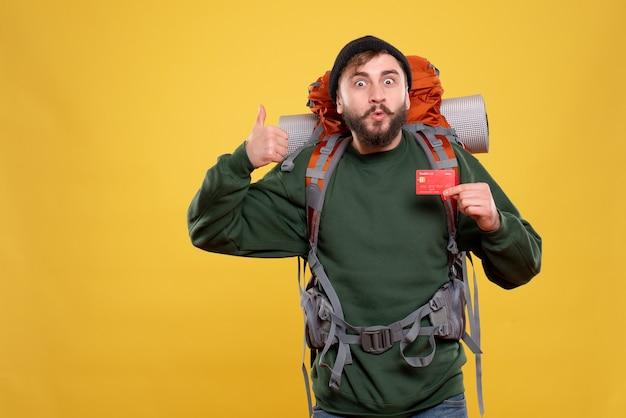 Conceito de viagens com um jovem confiante com packpack e segurando o cartão do banco, fazendo um gesto de ok em amarelo