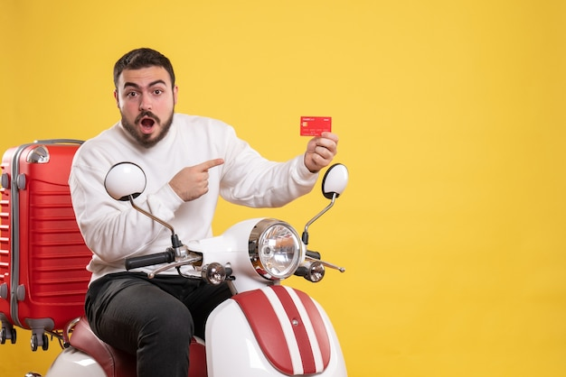 Conceito de viagens com um jovem confuso e emocional viajando, sentado em uma motocicleta com uma mala segurando o cartão do banco em amarelo