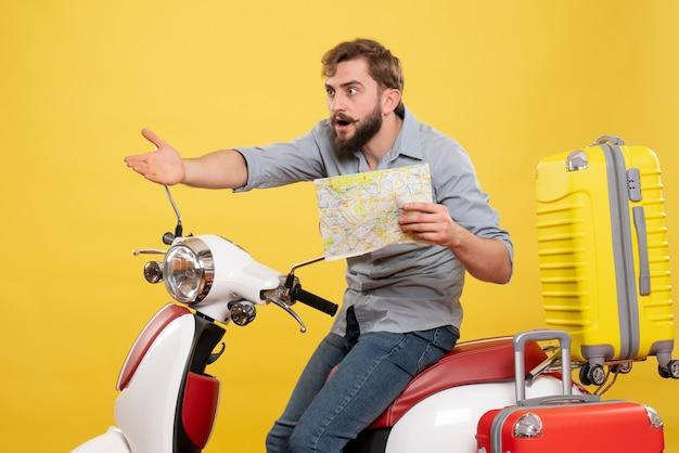 Conceito de viagens com um jovem curioso barbudo sentado na moto e mostrando o mapa em amarelo