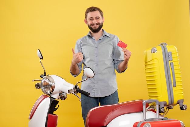 Conceito de viagens com um jovem sorridente em pé atrás de uma motocicleta com malas e fazendo um gesto de ok em amarelo
