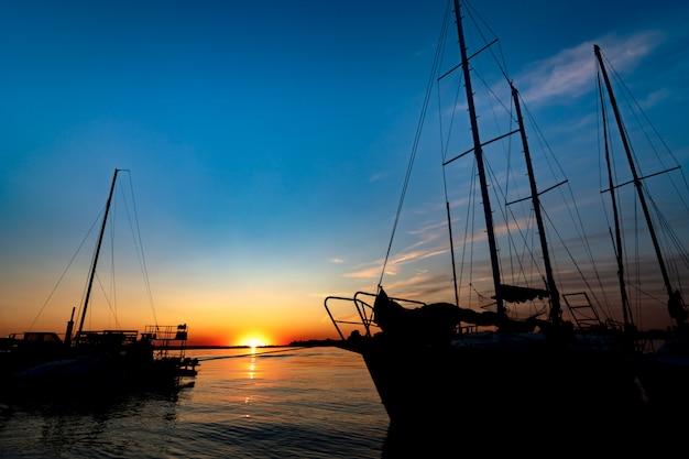Conceito de viagens de férias férias: nascer do sol do sol férias férias veleiro iate no cais. náutico, relaxamento