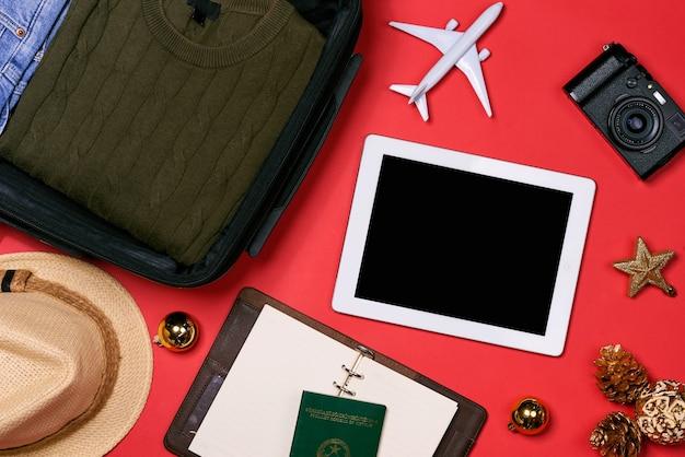 Conceito de viagens de férias - passaporte, câmera, chapéu, avião, decorações de natal em fundo vermelho