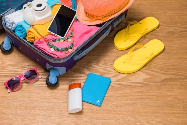 Conceito de viagens e férias. abra a bolsa de viagem com roupas, acessórios, cartão de crédito, passagens e passaporte.