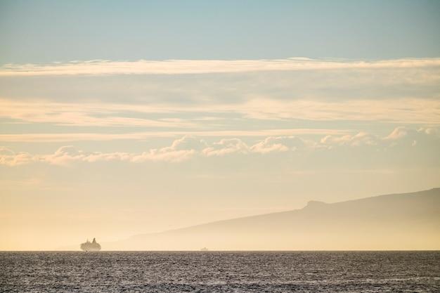 Conceito de viagens e férias com dois barcos de cruzeiro na linha do horizonte durante um lindo pôr do sol perto de uma ilha tropical no oceano